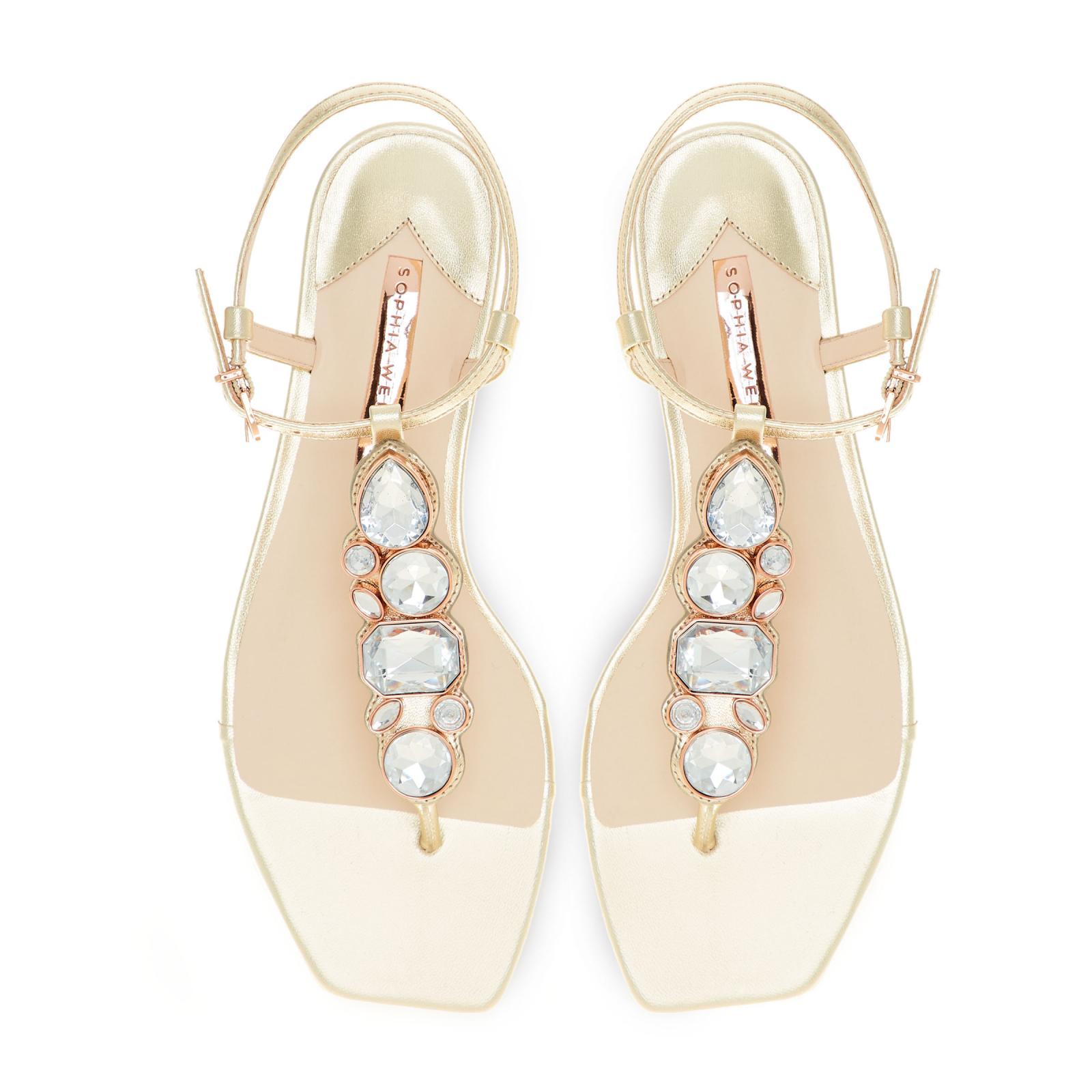 RITZY FLAT SANDAL Una delle nostre scarpe più luccicanti fino ad oggi, vorremmo presentarvi, la Ritzy. Questo sandalo flat è realizzato con una tomaia in pelle color champagne, rifinita con grandi gemme argentate.